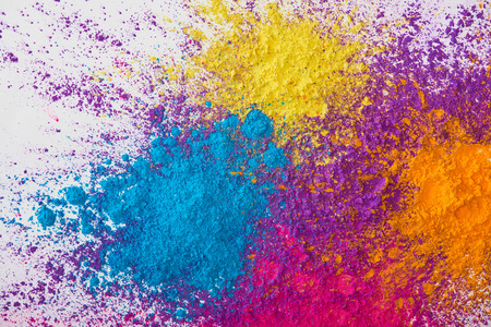 vista dall'alto dell'esplosione di polvere di holi gialla, viola, arancione e blu su sfondo bianco Archivio Fotografico