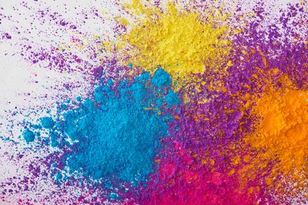 Vista superior de la explosión de polvo de holi amarillo, morado, naranja y azul sobre fondo blanco. Foto de archivo