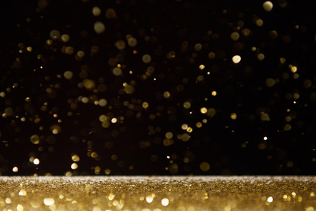 selective focus of golden shiny sparkles falling on table isolated on black