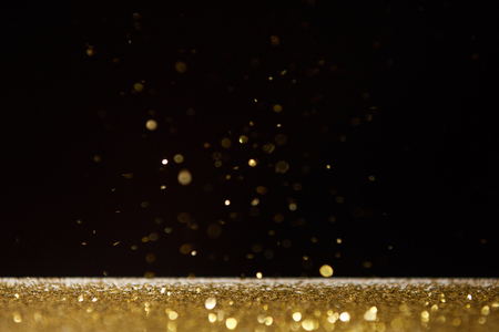 selective focus of bright golden sparkles on table isolated on black