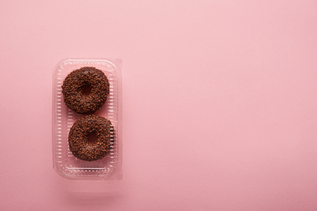 top view of chocolate donuts on pink background