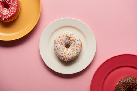top view of sweet delicious donuts on plates on pink background