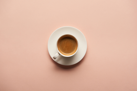 top view of tasty espresso in white cup on pink background