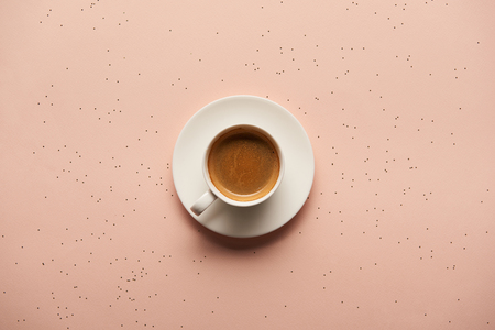 top view of hot coffee in white cup on pink background