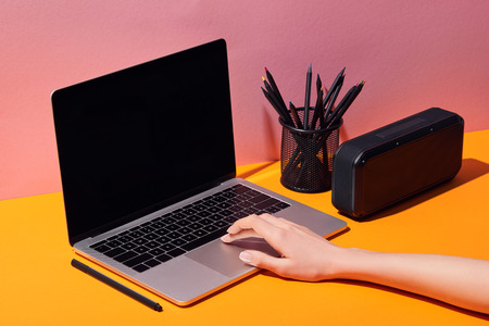 cropped view of woman using laptop with blank screen near pencil holder and speaker