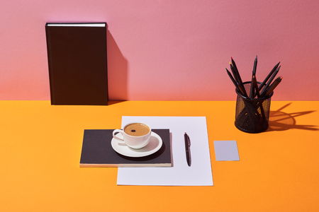 coffee cup, saucer, pen, paper sheet, pencil holder and notebook on yellow desk and pink background Stock Photo