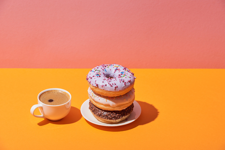 tasty donuts on saucer and coffe cup on yellow desk and pink background