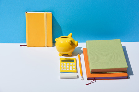 multicolored notebooks, calculator and piggy bank on white desk and blue background Foto de archivo - 116408252