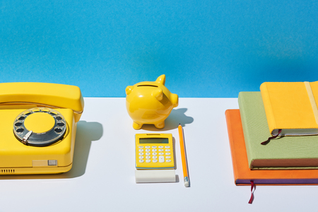 multicolored notebooks, calculator, telephone and piggy bank on white desk and blue background Stock Photo
