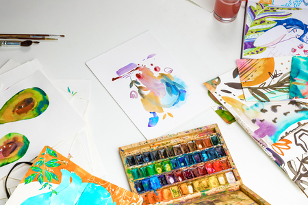 selective focus of colorful paints and watercolor drawings on white background
