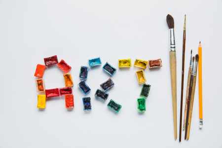 top view of paintbrushes, pencil and art lettering made of paints on white background Stock Photo