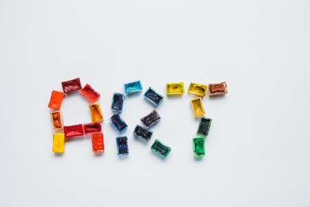 top view of art lettering made of paints on white background