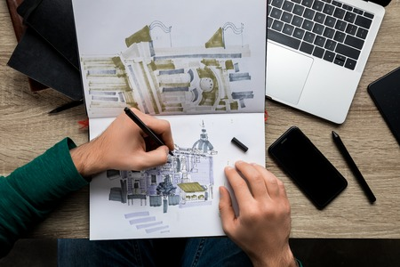 top view of mans hands drawing in album on wooden  table next to laptop and smartphone