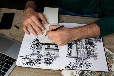 top view of mans hands drawing in notebook on wooden table next to albums and gadgets Stockfoto