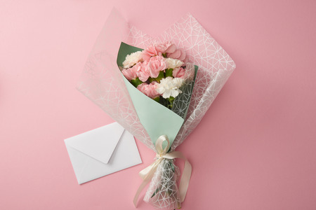 top view of beautiful tender flower bouquet and white envelope isolated on pink Stock Photo