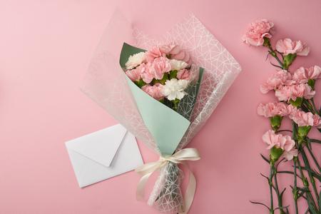 schöner Blumenstrauß, rosa Nelkenblumen und weißer Umschlag einzeln auf rosa