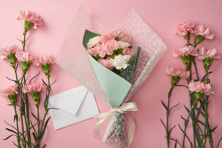 top view of beautiful bouquet, pink carnation flowers and white envelope isolated on pink