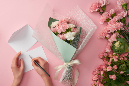 cropped shot of woman writing on greeting card and beautiful pink flower bouquet isolated on pink 免版税图像