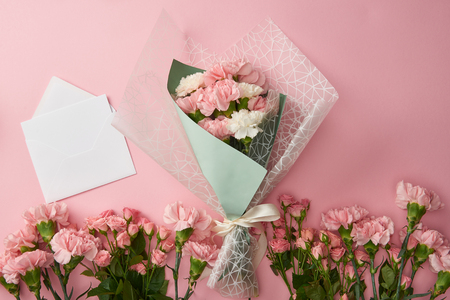 top view of beautiful bouquet, tender pink flowers and white envelope with card isolated on pink Stock Photo