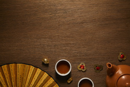 top view of tea set, fan with hieroglyphs and golden coins on wooden surface Banque d'images - 116408107