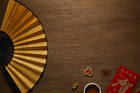 top view of fan with hieroglyphs, golden coins and cup of tea on wooden table Banque d'images - 116408106