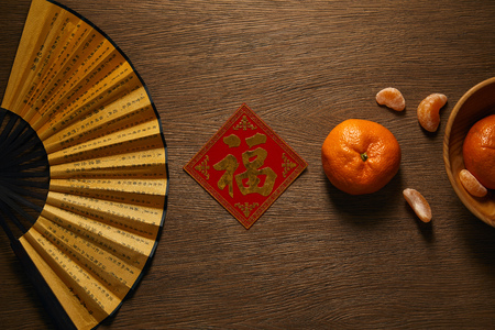 top view of fan, fresh ripe tangerines and decorative golden hieroglyph on wooden table 免版税图像