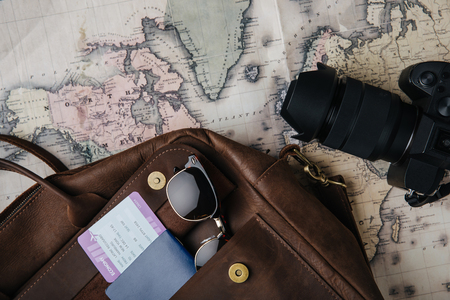 top view of leather bag with passport, ticket, sunglasses, camera and map Imagens