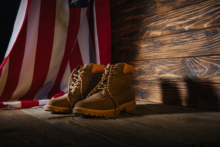 trekking boots and american flag on wooden surface, travel concept 免版税图像