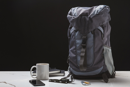 backpack, smartphone, cup, notebooks and compass on black, travel concept