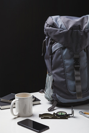 backpack, smartphone, cup and compass on black, travel concept Stock Photo