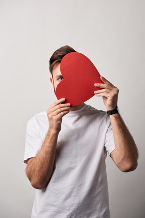 man hiding face behind blank paper cut heart card on grey background