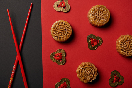 top view of mooncakes, feng shui coins and chopsticks on red and black background