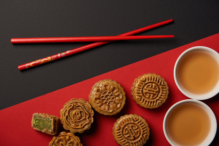 top view of traditional chinese mooncakes with chopsticks on red and black background Stock Photo
