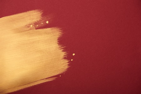 artistic burgundy wallpaper with golden brushstroke and copy space Standard-Bild