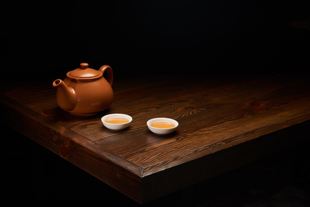 pot with traditional chinese tea and cups on wooden table isolated on black Reklamní fotografie