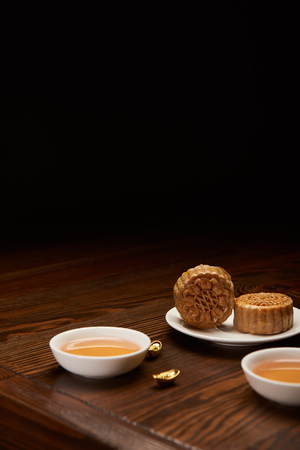 traditional mooncakes with tea cups and gold ingots isolated on black with copy space Stock Photo