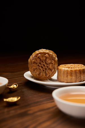 selective focus of mooncakes with tea cup and gold ingots isolated on black