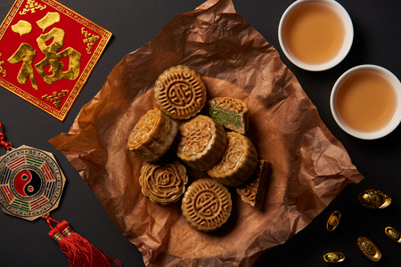 top view of traditional mooncakes with chinese talismans and tea isolated on black