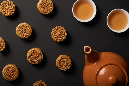 Top view of mooncakes, tea pot and cups isolated on black