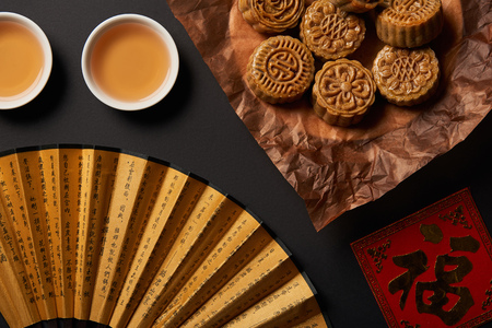 Top view of traditional chinese mooncakes with tea and hand fan isolated on black Stok Fotoğraf