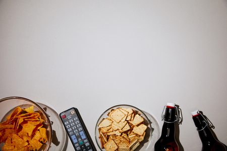 top view of glass bowls with tasty snacks near bottles and remote control on white background