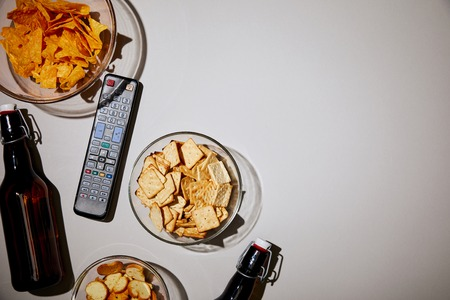 top view of bottles near remote control and snacks on white background