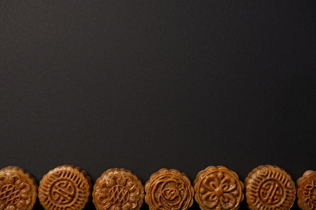 top view of traditional chinese mooncakes isolated on black with copy space
