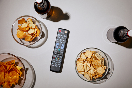 top view of bottles with beer near remote control and snacks on white background