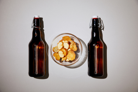 top view of brown bottles with beer near snack in bowl on white background Stock Photo