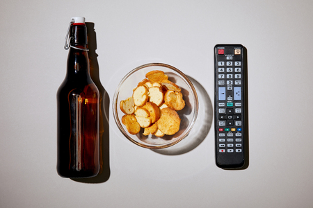 top view of brown bottle with beer near snack in bowl and remote control on white background Stock Photo - 116407748