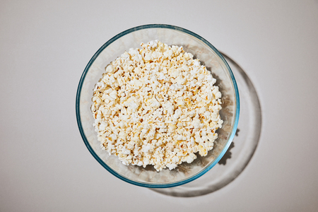 top view of tasty popcorn in bowl on white background