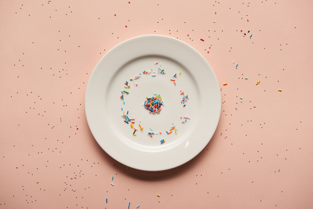 top view of white plate with sprinkles on pink background 版權商用圖片