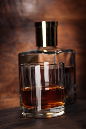 close-up view of glass of cognac and bottle on wooden table