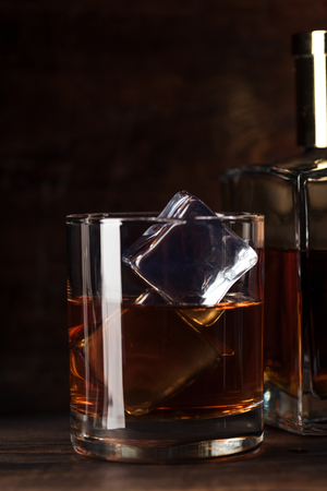 close-up view of glass of bourbon with ice cubes and bottle on wooden table Standard-Bild - 116407762